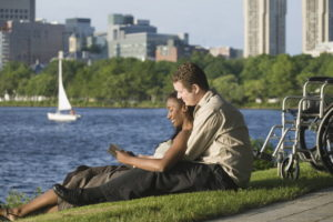 Side profile of a mid adult couple sitting in a park and reading a book.