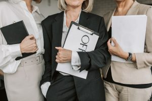 three business associates holding legal pads